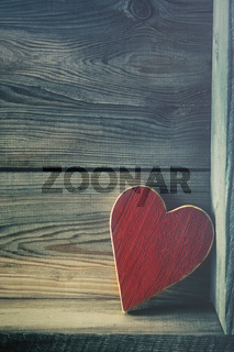 Red wooden heart on shelf