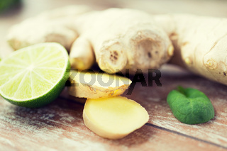 close up of ginger root and lime on wooden table