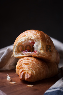 Closeup of croissant with jam and coffee on a wooden background. selective focus