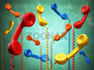 Telehone receivers of different colors hanging on the green background. Communication concept.