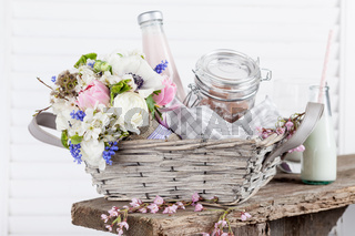 Sweet, rustic picnic basket with milk and flowers