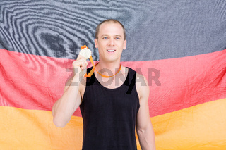 Athlete showing his gold medal in front of german flag