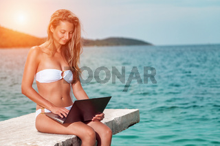 Woman sitting and relaxing on a beach  during holiday with a laptop