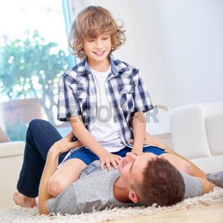 Vater und Junge toben im Wohnzimmer