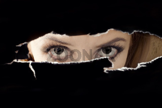 Women's eyes spying through a hole