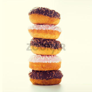 close up of glazed donuts pile over white