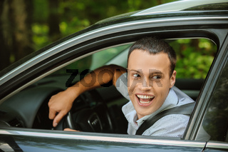 portrait of young man driving car and greeting somebody with hand