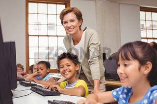 Cute pupil in computer class with teacher smiling at camera