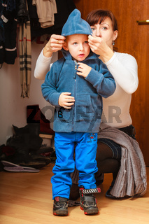 mother in front hallway putting on child coat