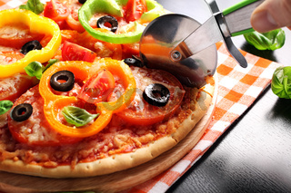 Vegetarian pizza with peppers, tomatoes, olives and basil