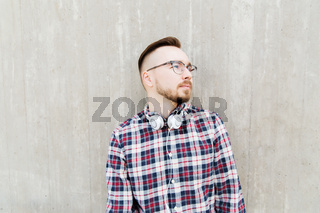 happy young hipster man with headphones over wall