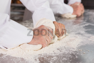 Close up of bakers kneading dough at counter