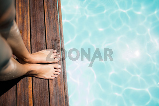 Woman feet on pools edge