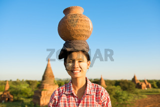 Young Asian traditional female farmer carrying clay pot on head