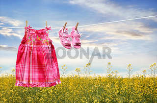 Dress and sandals on clothesline in summer