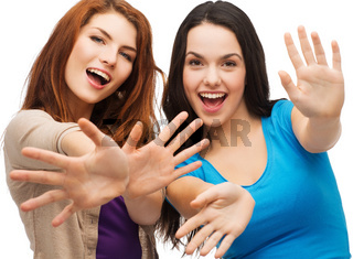 two smiling girls showing their palms