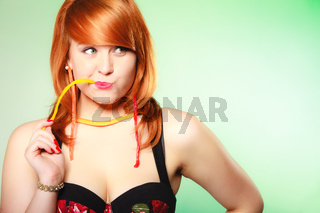 Redhair girl holding sweet food jelly candy on green.