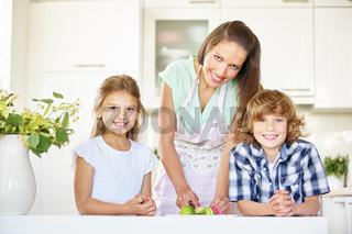 Mutter und Kinder schneiden fröhlich Limette