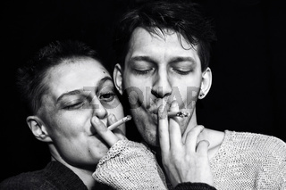 Young man and woman smoking cigarettes