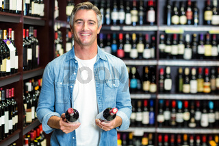 Smiling man holding bottles of wine
