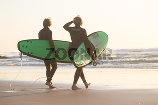 Surfers on beach with surfboard.