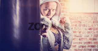 Composite image of portrait of female fighter in hood with fighting stance