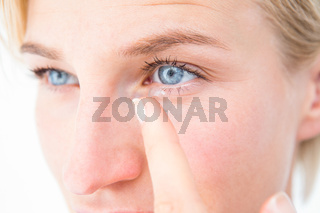 Pretty blonde applying contact lens