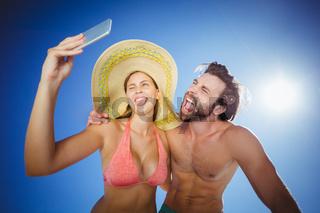 Couple taking selfie against blue sky