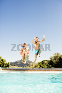 Happy couple jumping in the pool