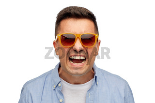 face of angry man in shirt and sunglasses