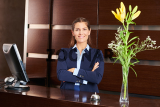 Frau am Empfang im Hotel lächelt freundlich