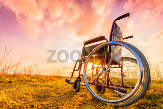 Empty wheelchair on the meadow at sunset