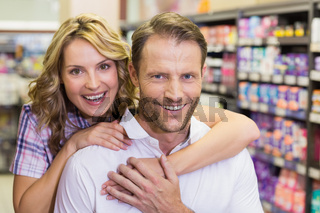 Portrait of smiling casual couple with arm aroung