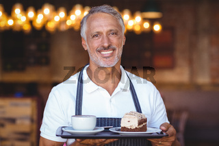 waiter smiling and holding tray