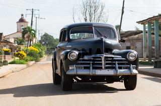 Schwarzer Oldtimer fährt in  Santa Clara Cuba