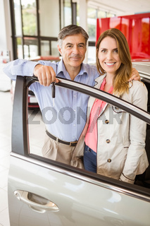 Smiling couple leaning on car