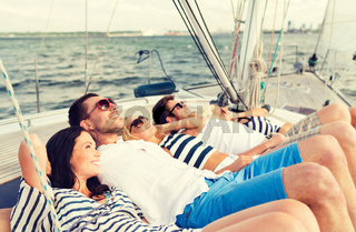 smiling friends lying on yacht deck
