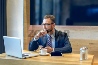 Businessman enjoying coffee and checking a mobile