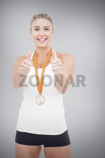 Composite image of female athlete wearing a medal and showing thumbs up