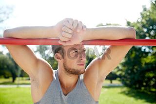 young man exercising on horizontal bar outdoors