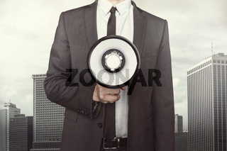 Businessman holding megaphone on cityscape background