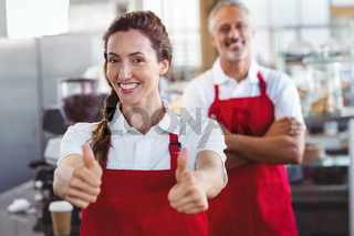 Smiling barista gesturing thumbs up with colleague behind