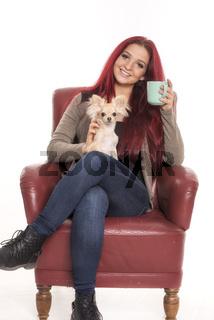 rothaarige frau mit einem chihuahua auf dem schoß trinkt kaffee