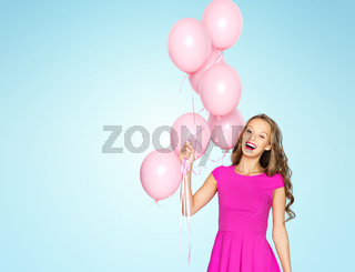 happy young woman with air balloons over blue