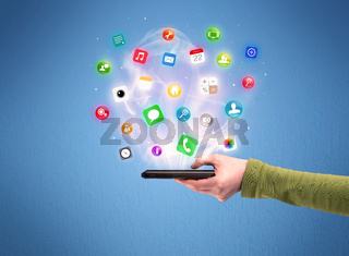 Hand holding tablet phone with app icons