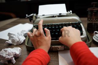 woman typing on old typewriter