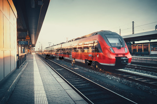 Beautiful railway station with modern red commuter train at sunset