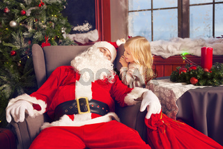 Photo of happy littlle smiling girl looking at sleeping Santa Claus