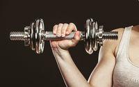 Closeup arm strong woman lifting dumbbells weights