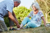 Mann hilft alter Frau mit verstauchtem Fuß